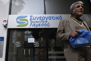 photo - An elderly man passes by a cooperative bank in Limassol, Cyprus, Saturday, March 16, 2013. Many rushed to the cooperative banks which are open Saturdays in Cyprus, after learning that the terms of a bailout deal that the cash-strapped country hammered out with international lenders, includes a one-time levy on bank deposits. The move, decided in an extraordinary meeting of the finance ministers of the 17-nation euro zone in the early hours Saturday, is a major departure from established policies.  (AP Photo/Pavlos Vrionides)