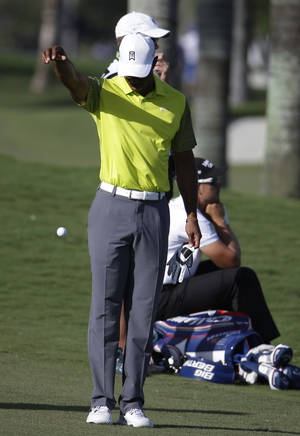 Photo - Tiger Woods takes a drop on the eighth hole during the second round of the Cadillac Championship golf tournament Friday, March 7, 2014, in Doral, Fla. More than 100 balls went into the water in the newly designed course. (AP Photo/Lynne Sladky)