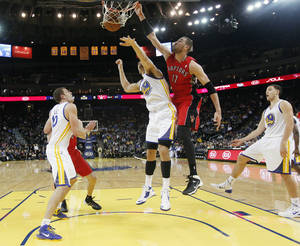 Photo - Toronto Raptors' Jonas Valanciunas (17) dunks over Golden State Warriors' Andrew Bogut (12) as Warriors' David Lee (10) and Klay Thompson (11) stand by during the first half of an NBA basketball game on Tuesday, Dec. 3, 2013, in Oakland, Calif. (AP Photo/Marcio Jose Sanchez)