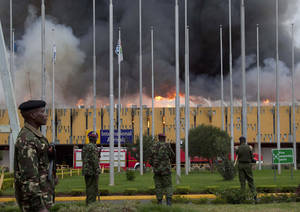 Photo - FILE - In this Wednesday, Aug. 7, 2013 file photo, police stand guard as fire engulfs the international arrivals unit of the Jomo Kenyatta International Airport, in Nairobi, Kenya.   Putting that disaster in the past , Kenya Airways' chief executive Titus Naikuni is predicting an exciting couple of years for African air travel, with new Boeing Dreamliners, the opening of a new terminal and, on the horizon, Kenya's first direct flights to the United States.(AP Photo/Sayyid Azim, File)
