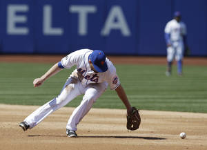 Photo - New York Mets second baseman Daniel Murphy commits a fielding error on a ball hit by Washington Nationals' Denard Span during the fourth inning of the baseball game at Citi Field, Thursday, April 3, 2014 in New York. (AP Photo/Seth Wenig)