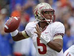 Photo - Florida State quarterback Jameis Winston looks for a receiver during the first half of an NCAA college football game against Florida in Gainesville, Fla., Saturday, Nov. 30, 2013.(AP Photo/John Raoux)