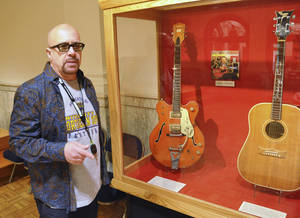 Photo - FILE - This April 22, 2013 file photo shows Memphis-based guitarist Robert Johnson standing by a display of guitars that belonged to Chet Atkins and Johnny Cash that he donated to the National Music Museum in Vermillion, S.D. Johnson also donated the guitar played by Elvis Presley during his final tour, but that may have to be taken off display. A lawsuit filed in July 2014 in South Dakota is seeking to determine who is the legal owner ofthe Elvis Presley guitar. A man now claims he is the owner of the slightly smashed acoustic guitar. (AP Photo/Dirk Lammers, File)