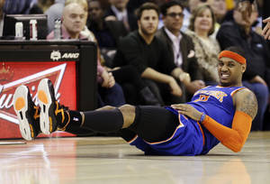 photo - New York Knicks' Carmelo Anthony grimaces after falling in the second quarter of an NBA basketball game against the Cleveland Cavaliers, Monday, March 4, 2013, in Cleveland. (AP Photo/Tony Dejak)