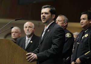 "photo -   Clark Settles, Homeland Security Investigations Special Agent in Charge, with local law enforcement representatives behind him, talks about the arrests of 13 members and associates of the 500 Block/C Street gang during a news conference in South San Francisco, Calif., Thursday, May 3, 2012. Three Immigration and Customs Enforcement agents were shot and injured Thursday while serving ""high-risk"" warrants in the San Francisco Bay area, authorities said. The agents suffered non-life threatening injuries during an early-morning raid in Petaluma in connection with a 2010 gang-related triple homicide. (AP Photo/Eric Risberg)"