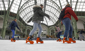 photo - Skaters take advantage of the giant ice rink set up under the famous glass roof of the Grand Palais, in Paris Thursday Dec. 13, 2012. The Grand Palais skating rink is the largest temporary ice rink ever created in France. It will remain open until Jan. 6, 2013.(AP Photo/Remy de la Mauviniere)
