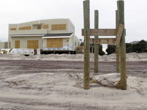 Photo -   In this Friday, Nov. 16, 2012 photo, pilings that once held a walkway over dunes leading to the beach are all that remain outside a boarded up home in Ocean Beach, N.Y. The Fire Island community was damaged in Superstorm Sandy. (AP Photo/Frank Eltman)
