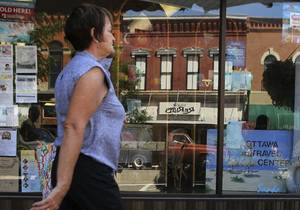 Photo - FILE - In this Aug. 1, 2013 file photo, a shopper strolls past a storefront in downtown Ottawa, Ill. The private Conference Board reports on consumer confidence for August on Tuesday, Aug. 27 , 2013. (AP Photo/NewsTribune, Genna Ord, File)