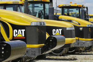 Photo - FILE - In this June 20, 2012 file photo, earth-moving tractors and equipment made by Peoria, Ill.-based Caterpillar Inc. are seen in Clinton, Ill.  Caterpillar and several mining companies have evacuated employees from Liberia. British Airlines has canceled flights to the region. Exxon and Chevron say they're waiting to see whether public health authorities can contain the Ebola outbreak in three West African countries. (AP Photo/Seth Perlman, File)