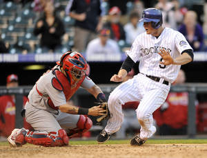 Photo - St. Louis Cardinals catcher Tony Cruz tags Colorado Rockies' DJ LeMahieu at home plate without the ball during the 15th inning of a baseball game Thursday, Sept. 19, 2013, in Denver. The Rockies won 7-6 in 15 innings. (AP Photo/Jack Dempsey)