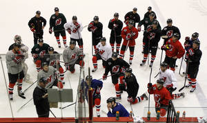 Photo - New Jersey Devils head coach Peter DeBoer, bottom left, writes on a board during the team's first official practice since the NHL hockey lockout ended, Sunday, Jan. 13, 2013, in Newark, N.J. (AP Photo/Julio Cortez)