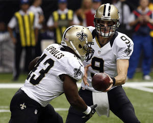 Photo - New Orleans Saints quarterback Drew Brees (9) hands off to running back Darren Sproles on a touchdown carry in the first half of an NFL football game in New Orleans, Monday, Sept. 30, 2013. (AP Photo/Bill Haber)