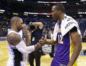 photo - Former teammates Orlando Magic's Jameer Nelson, left, and Los Angeles Lakers' Dwight Howard (12) shake hands before leaving the court at the end of an NBA basketball game, Tuesday, March 12, 2013, in Orlando, Fla. Los Angeles won the game 106-97.(AP Photo/John Raoux)