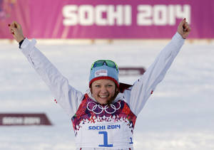 Photo - Norway's Maiken Caspersen Falla celebrates winning the gold medal during the flower ceremony for the women's cross-country sprint the 2014 Winter Olympics, Tuesday, Feb. 11, 2014, in Krasnaya Polyana, Russia. (AP Photo/Matthias Schrader)
