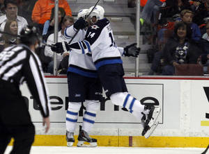 Photo - Winnipeg Jets right wing Anthony Peluso (14) leaps in celebration into left wing Eric Tangradi, left, after Tangradi scores in the second period of an NHL hockey game against the Anaheim Ducks Monday, March 31, 2014, in Anaheim, Calif. (AP Photo/Alex Gallardo)