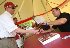 Photo - OU fan Blake Simon from Tulsa has a football signed by OU Football Head Coach Bob Stoops during the Sooner Caravan, taken in Tulsa, Okla, on June 6 2012. JAMES GIBBARD/Tulsa World