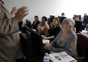 Photo - In this Thursday, Feb. 6,  2014, photo, Rosi Pozzi, 73, of Davie, Fla., right, listens during a job search workshop at WorkForce One, in Davie, Fla. Two straight weak job reports have raised doubts about economists' predictions of breakout growth in 2014. The global economy is showing signs of slowing again. (AP Photo/Lynne Sladky)