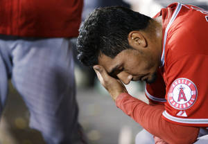 Photo - Los Angeles Angels pitcher Fernando Salas sits in the dugout after he was pulled in the seventh inning of a baseball game after giving up a solo home run to Seattle Mariners' Corey Hart, Tuesday, April 8, 2014, in Seattle. (AP Photo/Ted S. Warren)