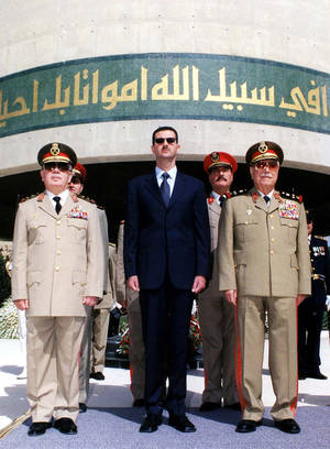 Photo -   FILE - In this Oct. 6, 2002 file photo, Syrian President Bashar Assad, center, with Syrian Defense Minister Mustafa Tlass, right, and Hassan Turkmany, Chief of Staff, visit the tomb of the unknown soldier, in Damascus, on the occasion of the 29th anniversary of their Liberation War, when Syria and Egypt launched surprise attacks against Israel on Oct. 6, 1973. A top general who has abandoned President Bashar Assad's regime was a longtime friend from Syria's most powerful Sunni family, and his break with the inner circle signals crumbling support from a privileged elite. Brig. Gen. Manaf Tlass was a commander in the powerful Republican Guard and the son of former defense minister Mustafa Tlass, who held the post for 32 years until he retired in 2004.(AP Photo/Sana, File)