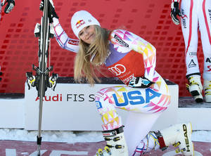 Photo - FILE - In this Dec. 7, 2011 file photo, Lindsey Vonn kneels down in front of the podium after winning the women's World Cup Super G  ski competition in Beaver Creek, Colo. Vonn was supposed to make her World Cup return this week on a course almost custom-made for her. But after re-injuring her knee last week, the four-time World Cup champ is sitting this one out. (AP Photo/Alessandro Trovati, File)
