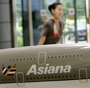 photo - FILE - In this July 19, 2005 file photo, an employee of Asiana Airlines walks past its model plane on display in Seoul. South Korea's human rights commission has recommended that the country's second-largest airline allow its female cabin crew to wear trousers, adding weight to a union campaign to ease strict dress rules. The commission's ruling made Monday, Feb. 2, 2013, is non-binding but represents a small victory for the 3,400 female flight attendants at Asiana Airlines Inc. Since last year, they have been asking the company to relax appearance requirements that range from how many hairpins they can wear to the length of their earrings. (AP Photo/Lee Jin-man, File)