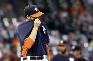 Photo - Houston Astros starting pitcher Collin McHugh wipes his face after giving up four runs to the Seattle Mariners in the third inning of a baseball game Sunday, May 4, 2014, in Houston. (AP Photo/Pat Sullivan)