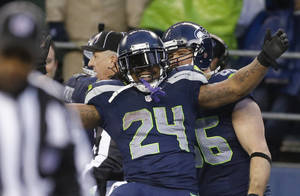 Photo - Seattle Seahawks running back Marshawn Lynch celebrates after running for a 31-yard touchdown against the New Orleans Saints during the fourth quarter of an NFC divisional playoff NFL football game in Seattle, Saturday, Jan. 11, 2014. (AP Photo/Ted S. Warren)