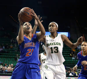 Photo - Houston Baptist guard Rachel Arthur (21) attempts a shot over Baylor forward Nina Davis (13), right, in the first half of an NCAA college basketball game, Sunday, Dec. 15, 2013, in Waco, Texas. (AP Photo/The Waco Tribune Herald, Michael Bancale)