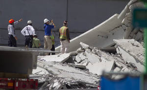 photo -   Rescue officials survey damage in the collapsed parking garage at the Miami Dade College West campus in Doral, Fla. Thursday, Oct. 11, 2012. One person is still missing. (AP Photo/J Pat Carter)