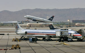 photo -   FILE - In this June 23, 2008 file photo, a US Airways jet takes-off as an American Airlines Jet is prepped for takeoff at Sky Harbor International Airport in Phoenix. The parent company of American Airlines has entered a non-disclosure agreement with U.S. Airways that will allow the companies to discuss combining the companies. AMR Corp., which is in Chapter 11 bankruptcy reorganization, and U.S. Airways Group Inc. said Friday, Aug. 31, 2012, that they've agreed not to talk to other parties about any potential combination while they are evaluating their situation with each other. (AP Photo/Matt York, File)