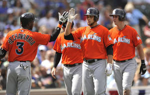 Photo - Miami Marlins' Henderson Alvarez, right foreground, celebrates with teammate Adeiny Hechavarria (3), after hitting a three-run home run during the second inning of a baseball game against the Chicago Cubs in Chicago, Monday, Sept. 2, 2013. (AP Photo/Paul Beaty)