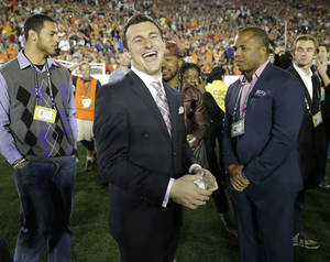 Photo - Texas A&M quarterback Johnny Manziel smiles from the sidelines during the first half of the NCAA BCS National Championship college football game between Auburn and Florida State Monday, Jan. 6, 2014, in Pasadena, Calif. (AP Photo/David J. Phillip)