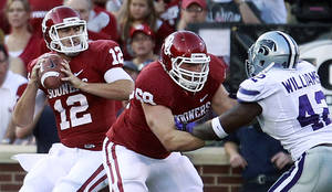 Photo -   Oklahoma quarterback Landry Jones (12) passes as Lane Johnson blocks Kansas State defensive end Meshak Williams (42) during the first quarter of an NCAA college football game in Norman, Okla., Saturday, Sept. 22, 2012. (AP Photo/Sue Ogrocki)