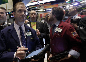 """Photo - Michael Smyth, left, works with fellow traders on the floor of the New York Stock Exchange, Wednesday, March 26, 2014.  The stock market opened higher Wednesday after a strong report on American manufacturing. The maker of the hit game """"Candy Crush Saga"""" flopped in its market debut.(AP Photo/Richard Drew)"""