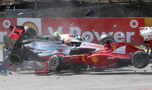 Photo -   McLaren Mercedes driver Lewis Hamilton of Britain, yellow helmet left, crashes with Ferrari driver Fernando Alonso of Spain, right, during the first lap of the Belgian Formula One Grand Prix in Spa-Francorchamps, Sunday, Sept. 2, 2012. (AP Photo/Luca Bruno)