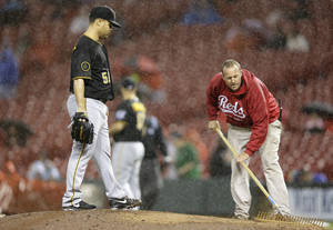 Photo - Pittsburgh Pirates starting pitcher Wandy Rodriguez (51) waits on the mound while a member of the Cincinnati Reds ground crew works on the mound in the fifth inning of a baseball game being played in the rain, Monday, April 14, 2014, in Cincinnati. (AP Photo/Al Behrman)