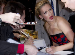 Photo -   U.S actress Scarlett Johansson signs autographs for fans as she arrives for the European Premiere of 'Marvel Avengers Assemble', at a west London cinema, Thursday, April 19, 2012. (AP Photo/Joel Ryan)