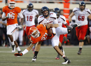photo - Oklahoma State's Lyndell Johnson (27) recovers a fumble in front of Texas Tech's Seth Doege (7) during a college football game between Oklahoma State University (OSU) and Texas Tech University (TTU) at Boone Pickens Stadium in Stillwater, Okla., Saturday, Nov. 17, 2012.  Photo by Bryan Terry, The Oklahoman