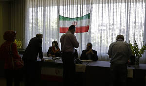 Photo - Iranians outside their country of origin sign in to cast ballots in Iran's presidential election,  in a hotel meeting room  in Los Angeles Friday, June 14, 2013. Iranian-Americans and expatriates cast ballots Friday in polling places across the United States, joining their countrymen half a world away in selecting the next Iranian president (AP Photo/Reed Saxon)