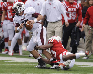 Photo -   Louisiana-Monroe quarterback Kolton Browning (15) is taken down by Western Kentucky linebacker Xavius Boyd (13) during the first half of an NCAA college football game in Bowling Green, Ky., Saturday, Oct. 20, 2012. (AP Photo/Daily News, Joe Imel)