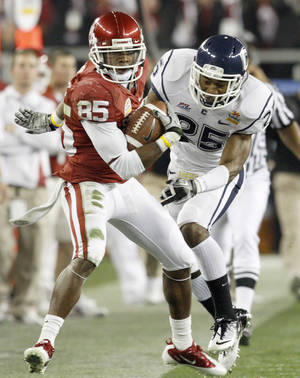 photo - Oklahoma's Ryan Broyles (85) gets pushed out by Connecticut's Harris Agbor (25) during the Fiesta Bowl. <i>The Oklahoman</i> columnist Berry Tramel thinks Broyles will return for his senior season at OU. Photo by Bryan Terry, The Oklahoman
