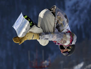 Photo - United States' Sage Kotsenburg takes a jump during the men's snowboard slopestyle semifinal at the Rosa Khutor Extreme Park, at the 2014 Winter Olympics, Saturday, Feb. 8, 2014, in Krasnaya Polyana, Russia. (AP Photo/Sergei Grits)