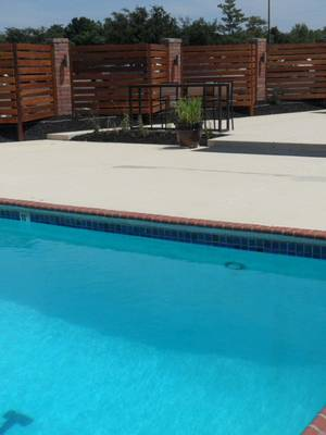 Photo - The Greens hired eight more seasonal workers than last year, partly because of increased interest sparked by remodels to its pool area. Pictured is the club's new brick and redwood fence to match the pool cabanas. PHOTO PROVIDED, <strong></strong>