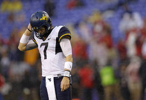 Photo - West Virginia quarterback Ford Childress walks off the field after Maryland gained possession of the ball on a fumble by running back Wendell Smallwood in the second half of an NCAA college football game in Baltimore, Saturday, Sept. 21, 2013. Maryland won 37-0. (AP Photo/Patrick Semansky)
