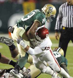 Photo - Austin Box (12) tackles Jay Fihnley (23) during the first half of the college football game between the University of Oklahoma Sooners (OU) and the Baylor Bears (BU) at Floyd Casey Stadium on Saturday, November 20, 2010, in Waco, Texas.   Photo by Steve Sisney, The Oklahoman