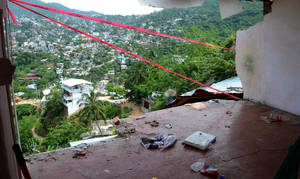 Photo - The wall of a home is missing after it fell during an earthquake in Acapulco, Wednesday, Aug. 21, 2013. The U.S. Geological Survey said the quake had a magnitude of 6.2 and was centered on the Pacific coast, near the resort of Acapulco.  (AP Photo/Bernardino Hernandez)