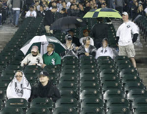 photo -   Chicago White Sox fans shelter themselves from the rain and watch a live broadcast of the Bears Green Bay Packers game on the big screen during a rain delay of a baseball game between the White Sox and the Detroit Tigers Thursday, Sept. 13, 2012, in Chicago. (AP Photo/Charles Rex Arbogast)