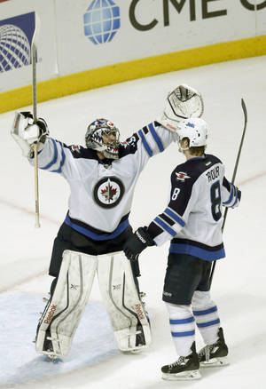 Photo - Winnipeg Jets goalie Al Montoya celebrates the Jets' 3-1 win over the Chicago Blackhawks with Jacob Trouba after an NHL hockey game Sunday, Jan. 26, 2014, in Chicago. (AP Photo/Charles Rex Arbogast)