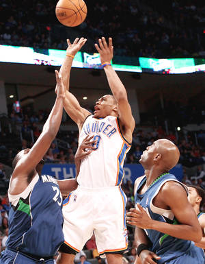 Photo - Thunder point guard Russell Westbrook puts up a shot over Minnesota's Al Jefferson, left, and Damien Wilkins during OKC's 116-108 win Sunday.  PHOTO BY JOHN CLANTON, THE OKLAHOMAN