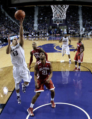 photo - Kansas State guard Angel Rodriguez (13) gets past Oklahoma guard/forward Cameron Clark (21) to put up a shot during the second half of an NCAA college basketball game on Saturday, Jan. 19, 2013, in Manhattan, Kan. Kansas State won the game 69-60. (AP Photo/Charlie Riedel)